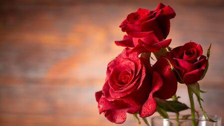 Red rose in vase on old wooden, Vintage style