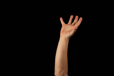 The hand of a young man on a black background close up