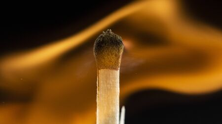 Burning wooden match with a red match head on a black background. Close up Фото со стока