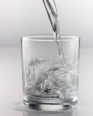 spray water in a glass on a gray background close up