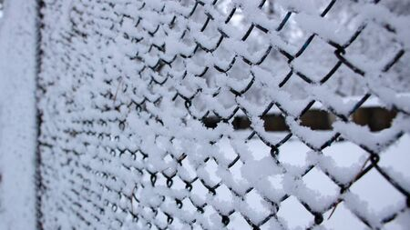 Old metal mesh fence in the snow on a cloudy winter day background Standard-Bild - 126475357
