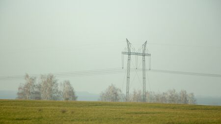 High voltage electricity transfer lines and pylon in a foggy morning Banque d'images - 130697421