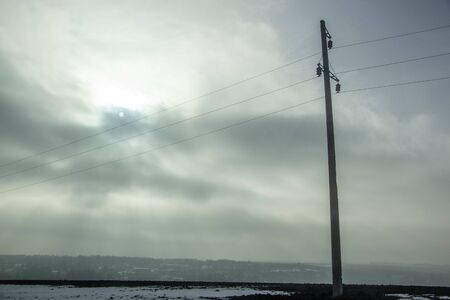 High voltage electricity transfer lines and pylon in a foggy morning Banque d'images - 130697429