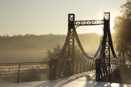 A railway bridge in the morning fog or smoke through which the rays of the sun shine background.