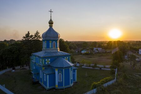 Old wooden church with metal roof. Located in a small village drone view