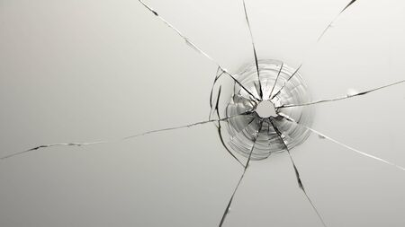 Cracks in a bullet punched glass, for use in design and special effects.