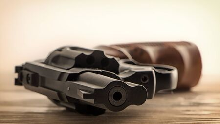 Front view of a black revolver lying on a wooden surface, soft focus, low depth of field