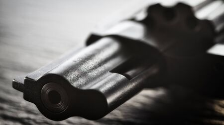 The black revolver lies on a dark shale surface. Closeup front view, soft focus