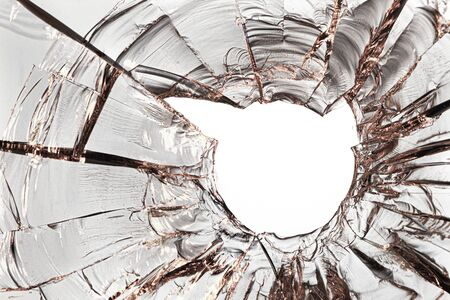Golden cracks in the glass, with a hole from the ball in the center, on a white background 写真素材