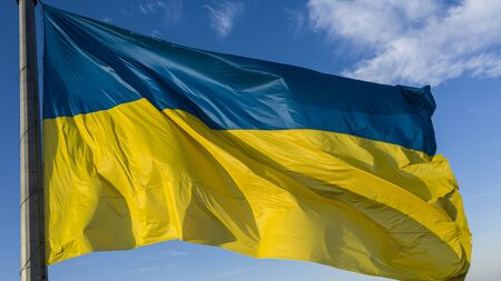 The Ukrainian flag flutters in the wind, against a blue sky with white clouds.