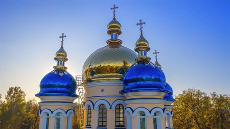 Yellow and blue gilding of the Ukrainian Orthodox Church. Drone view. On sunset background