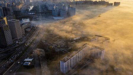 Autumn morning fog creeping into the city, the tops of high-rise buildings look like fog. 写真素材