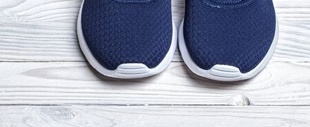 ancestors of blue high quality running shoes on white wooden background closeup.