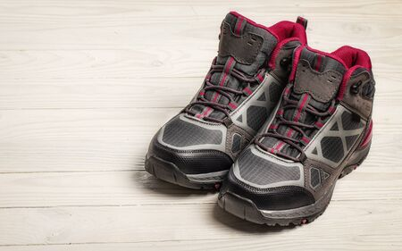 Female hiking boots on white wooden background Stockfoto
