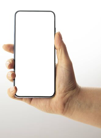 Luina holds a black smartphone in her hand, with a white and big screen, on a light background.