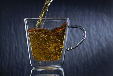 Tea is poured into a glass cup, on a dark background