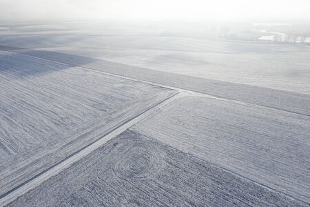 Winter landscape. Empty agricultural fields and trees covered with snow.