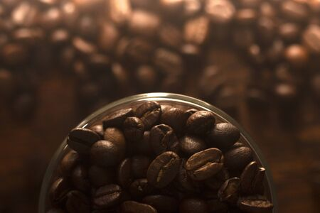 Background with coffee seeds in glass mug on wooden table