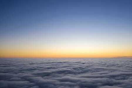 Yellow and blue dawn over clouds, concept, travel and leisure. 版權商用圖片