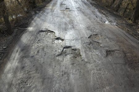 Bad asphalt road with pits filled with water. 版權商用圖片