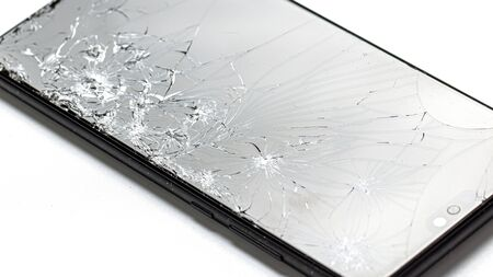 Broken black smartphone closeup on a white background. The display is covered by a crack grid.