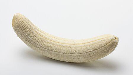 whole peeled banana on a white background