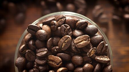 Background with coffee seeds in glass mug on wooden table, top view. Closeup, soft focus. 版權商用圖片