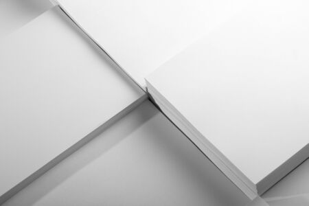 Several stacks of white paper on a white background