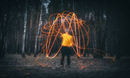 A man makes sparks from steel wool, or cotton wool, in an autumn deciduous forest. Mystical background, soft focus.