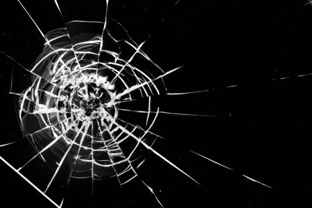 Round cracks in glass on black background. The hole in the glass surface from the bullet.