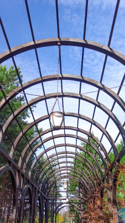 Sturdy large wooden arch with vintage lanterns on chains, against a blue sky background, in a garden for tall plants.
