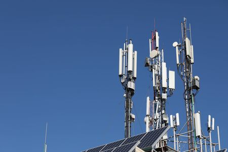 Many mobile towers, satellites and repeaters on a background of blue sky. Wireless communication equipment.