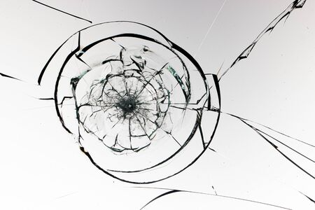 Round cracks in glass on white background. The hole in the glass surface from the bullet.