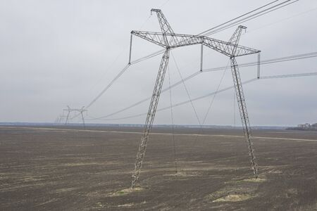 Large metal supports of power lines passing through agrarian fields to the horizon. 写真素材