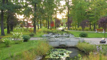 A small bridge in a summer green park. Stylized in antiquity, with bike and pedestrian walkway. In the shade of large pines and oaks. Creating a cool on a hot summer day.
