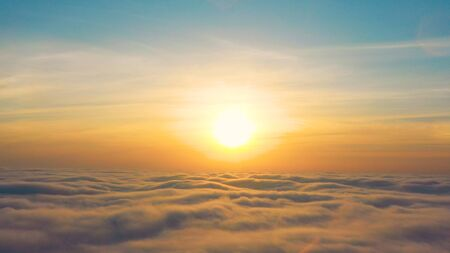 Dawn or sunset over the clouds. View from the plane. Relaxation meditation and travel concept.