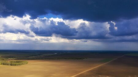 Storm clouds over agricultural fields in the countryside.