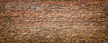 The brick wall has long been exposed to the aggressive environment. Deep seams. Old brick. Results of wind and rain erosion on bricks.