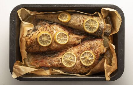 Baked fish in a baking dish on a white background.