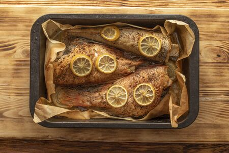 Three large baked fish with lemon on parchment paper in an oven tray on an old wooden table.