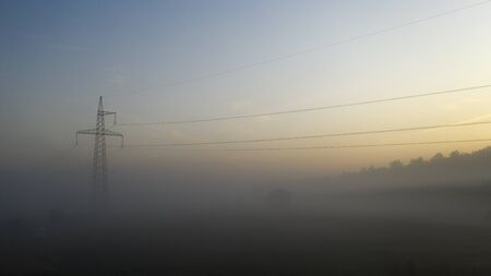 High voltage electricity transfer lines and pylon in a foggy morning