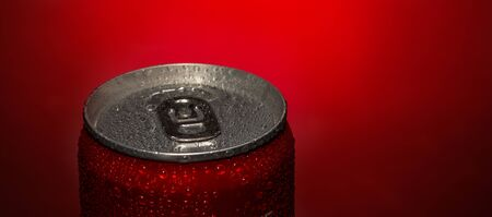 Opened aluminum can for soft drinks or beer with water drops on red background close up