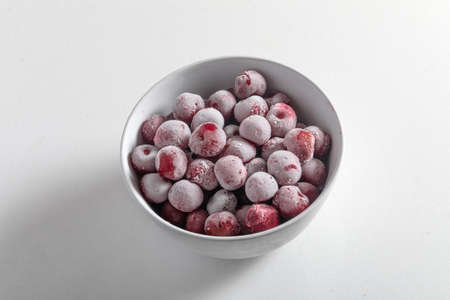 frozen cherries or cherries covered with hoarfrost in a white plate on a light background.