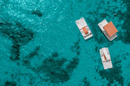 Top view of three catamarans drifting in shallow water.