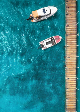 Motor boat and yacht near the wooden pier. Drone type. Banque d'images