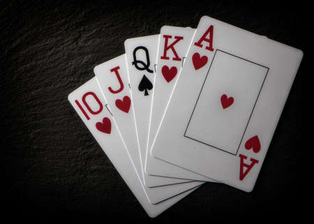 Poker hand. Incomplete Royal Flash on a black background.