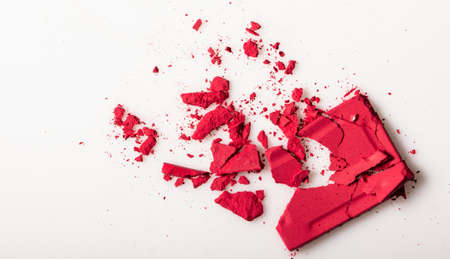 Red cosmetic powder on a white background