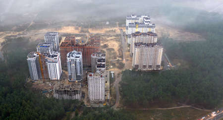 The tops of high-rise buildings above the fog. Drone view.