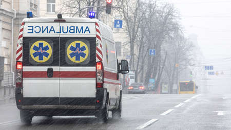 An ambulance took the patient to the clinic with the turn signals on. Bad weather outside, rain with wet snow. 免版税图像