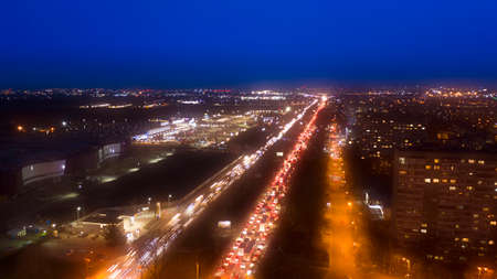 Evening traffic jams in the city, heavily congested roads and interchanges, transport collapse. Aerial view.